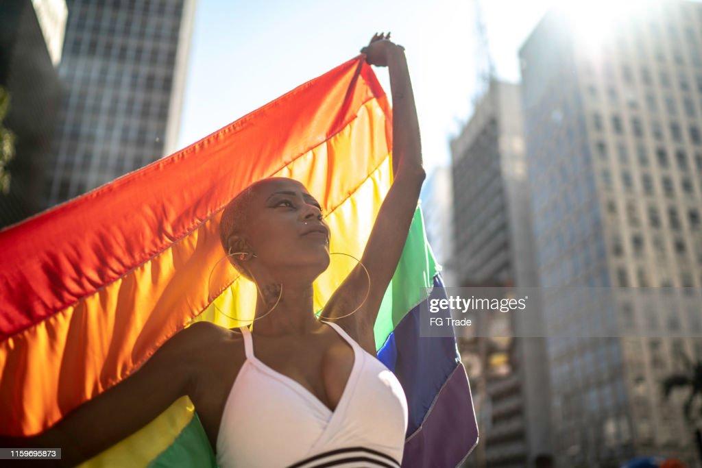 プライドパレード中に虹の旗を持つ自信のあるレズビアンの女性 : ストックフォト
