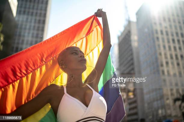 confident lesbian woman holding rainbow flag during pride parade - pride stock pictures, royalty-free photos & images