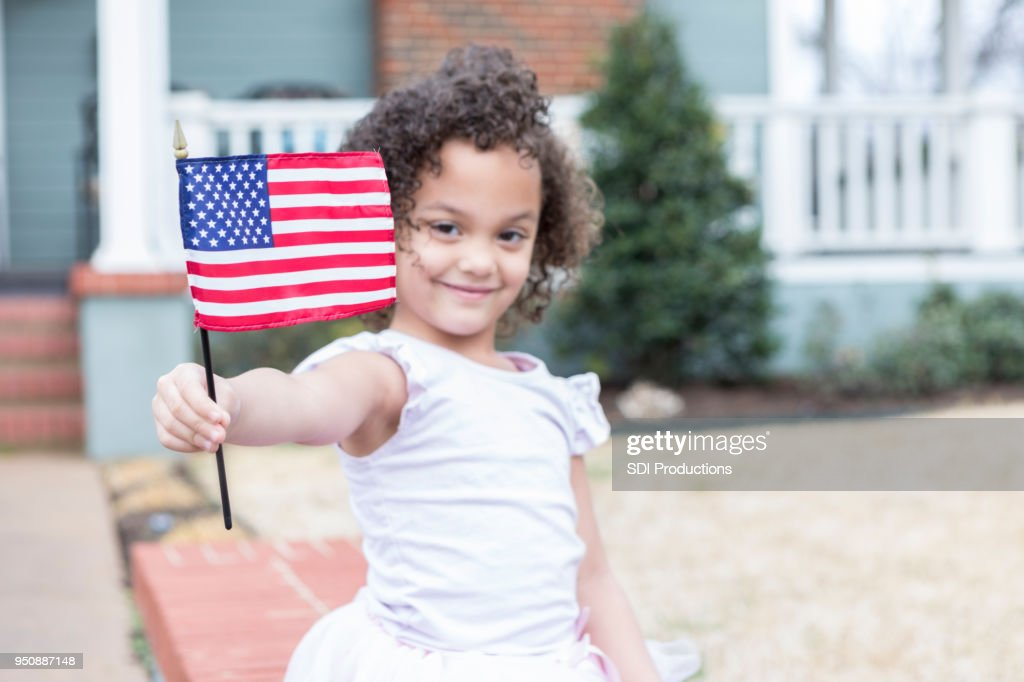 Confident little girl in front yard with American flag : Stock Photo