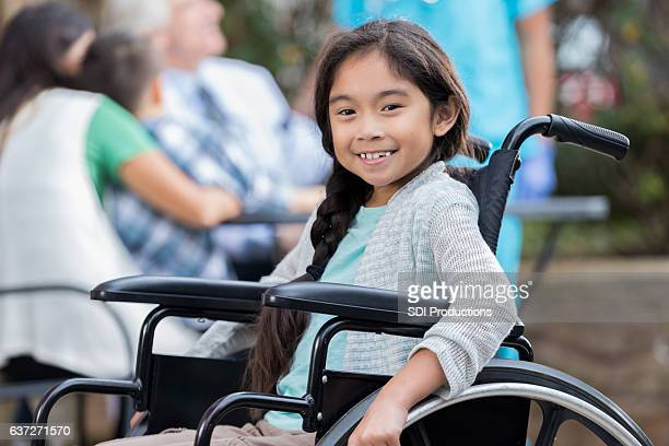 Confident little girl in wheelchair at outdoor clinic