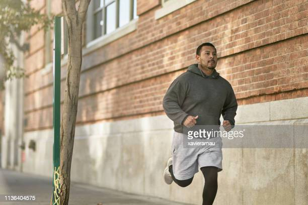 confident male athlete jogging on sidewalk in city - heavy stock pictures, royalty-free photos & images