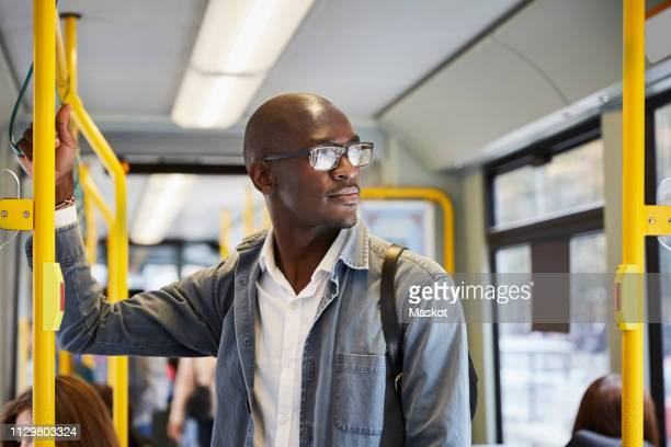 confident male commuter looking away while standing in tram - commuter stock pictures, royalty-free photos & images