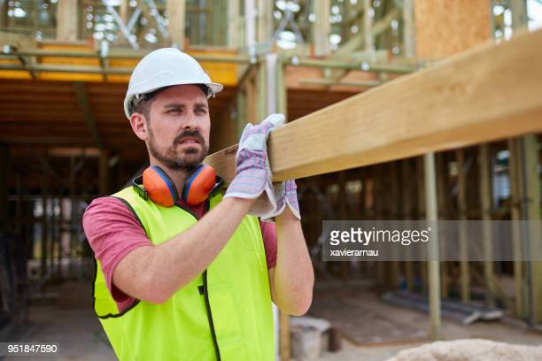 confident male construction worker carrying wood - carrying stock pictures, royalty-free photos & images