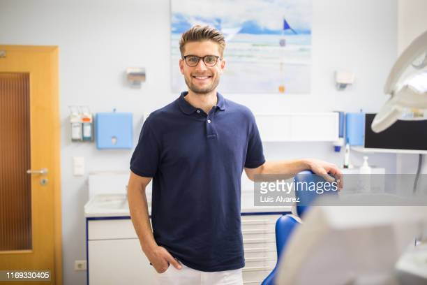confident male dentist standing in his clinic - polo shirt stock pictures, royalty-free photos & images