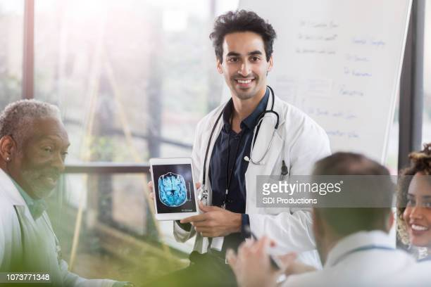 confident male doctor discusses human brain - hospital machine stock photos and pictures