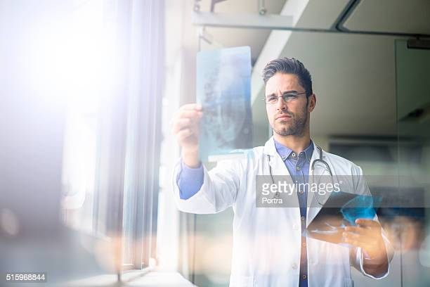 Confident male doctor examining x-ray in hospital