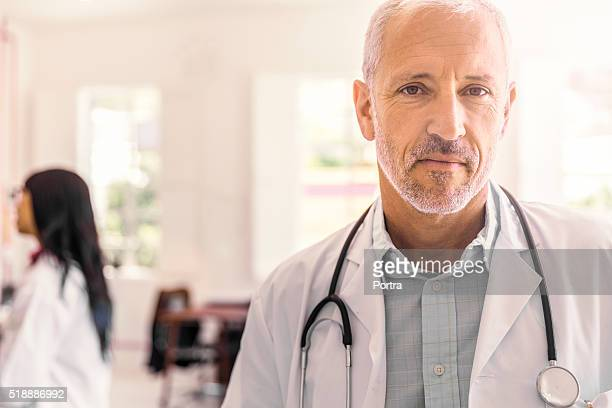 Confident male doctor in brightly lit clinic