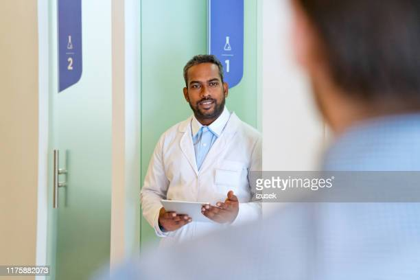 confident male doctor looking at man in corridor - building entrance stock pictures, royalty-free photos & images
