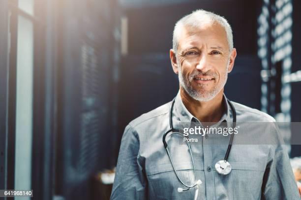 zuversichtlich männlichen arzt mit stethoskop in klinik - hausarzt stock-fotos und bilder
