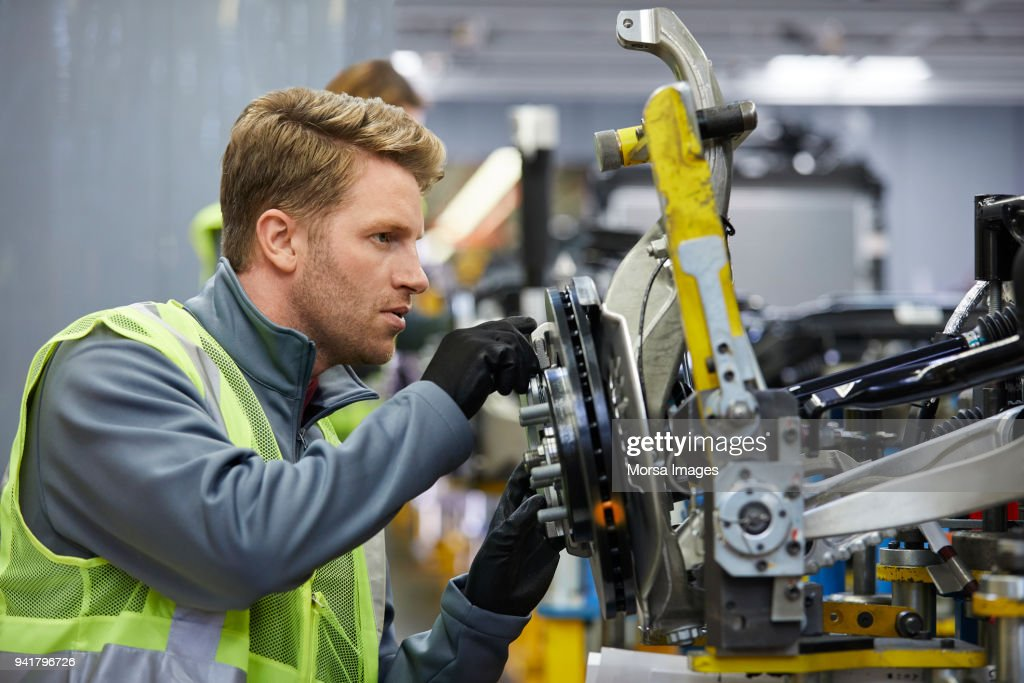 Confident male engineer examining car chassis : Stock Photo