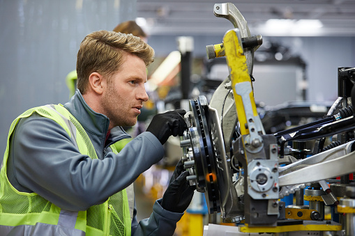 Confident male engineer examining car chassis 941796726