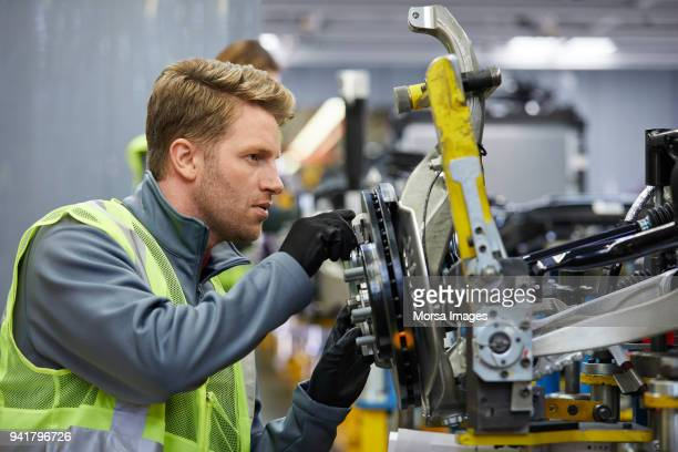Confident male engineer examining car chassis