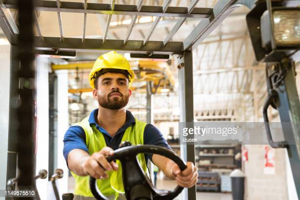 confident male engineer using forklift in factory - izusek stock pictures, royalty-free photos & images