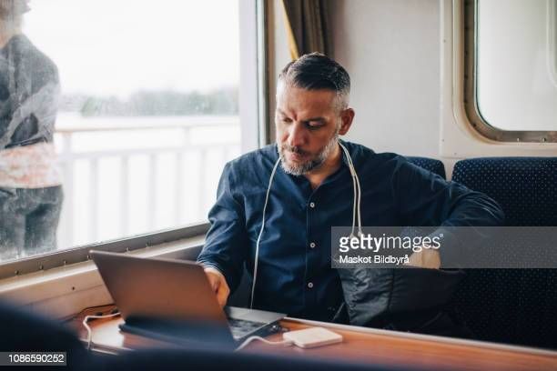 confident male entrepreneur using laptop by window while traveling in ferry - passagier wasserfahrzeug stock-fotos und bilder