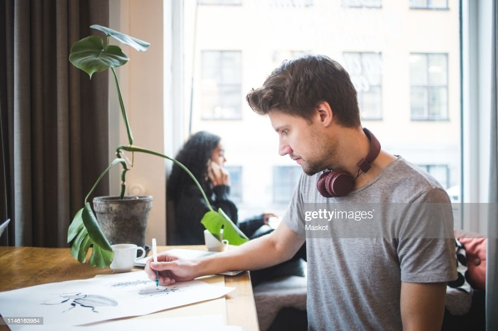 Confident male graphic designer drawing on paper at table in office : Stock Photo