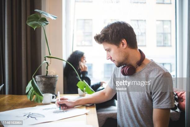 confident male graphic designer drawing on paper at table in office - illustrator stock photos and pictures