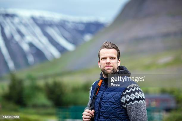 Confident male hiker standing against mountains