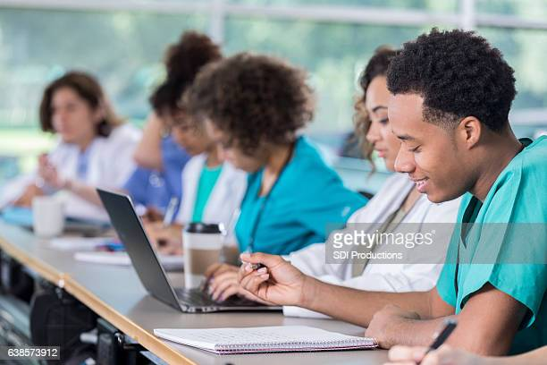 Confident male medical student takes notes in class