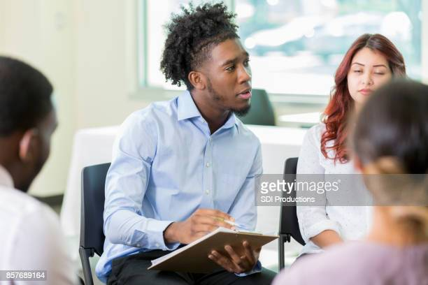 confident male mental health professional leads support group - vulnerability stock photos and pictures