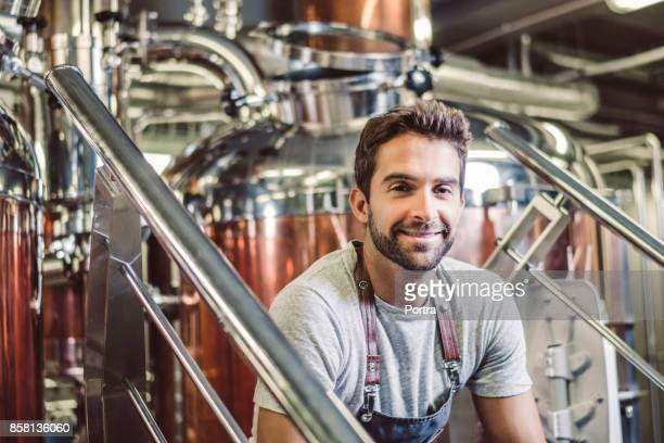 Confident male owner sitting at microbrewery