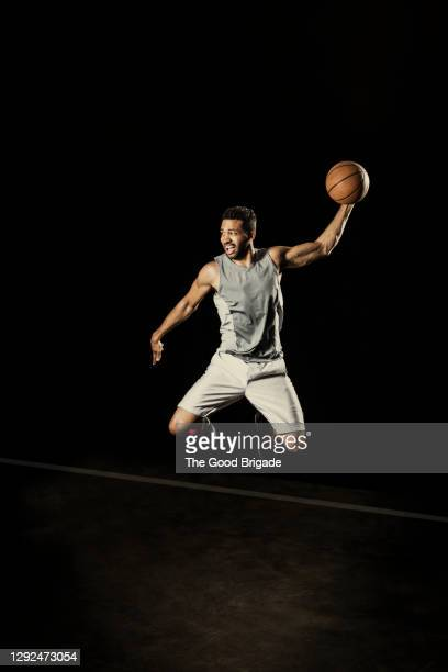 confident male player jumping with basketball against black background - try scoring stock pictures, royalty-free photos & images