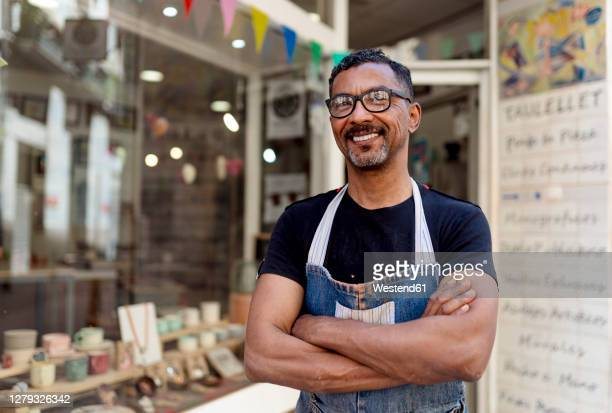 confident male potter with arms crossed standing outside ceramic shop - artist stock pictures, royalty-free photos & images
