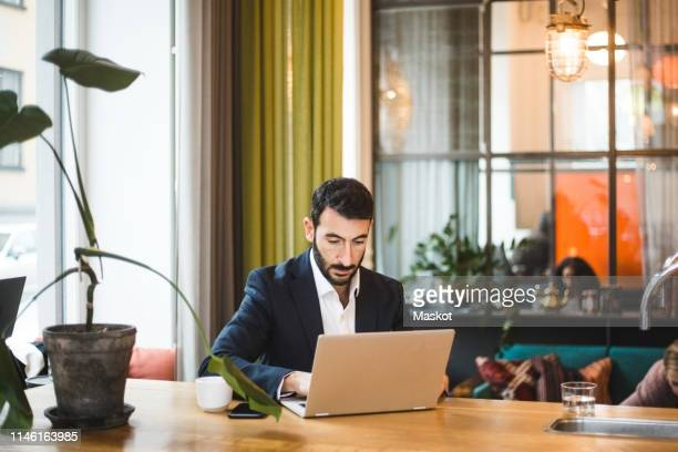 confident male professional using laptop while sitting at table in office - incidental people stock pictures, royalty-free photos & images