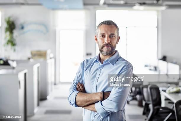 profesional masculino seguro con los brazos cruzados - only men fotografías e imágenes de stock