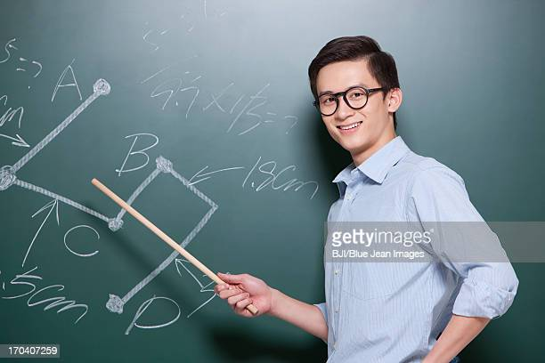 Confident Male teacher giving lessons in classroom