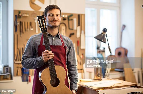Confident male worker holding guitar