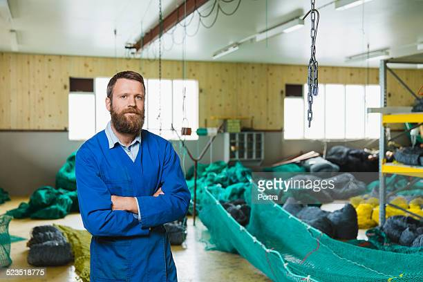 Confident male worker standing at fishing industry