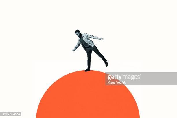 confident man balancing on orange semi-circle - 不均衡 ストックフォトと画像