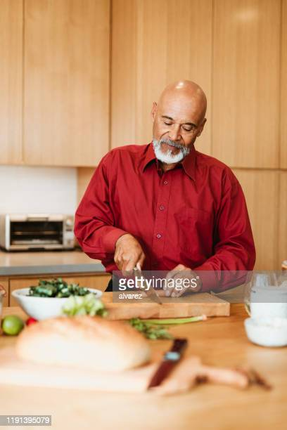 confident man chopping carrot at kitchen island - chopped stock pictures, royalty-free photos & images