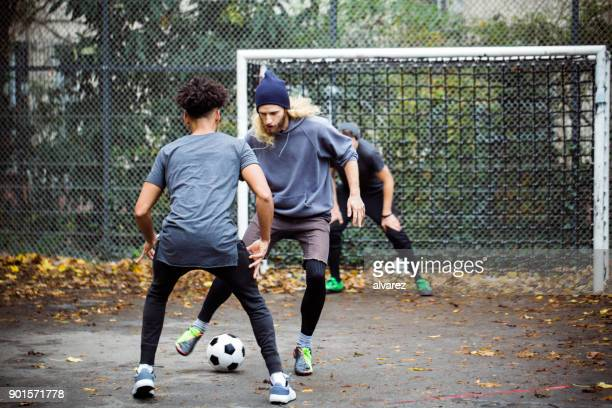 confident man dribbling ball from opponent - match sportivo foto e immagini stock