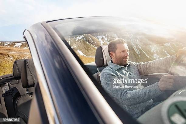 Confident man driving open roof top car.