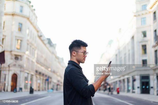 confident man exploring the city with smartphone - text stock pictures, royalty-free photos & images