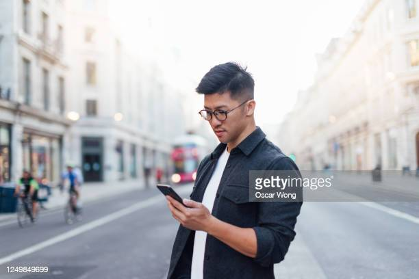 confident man exploring the city with smartphone - finance and economy stock pictures, royalty-free photos & images
