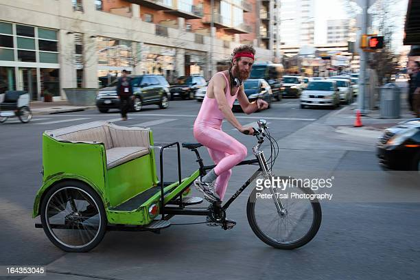 Confident man in a pink unitard and red headband zooms by and points at the camera while driving a green pedicab during SXSW 2013 on the streets of...
