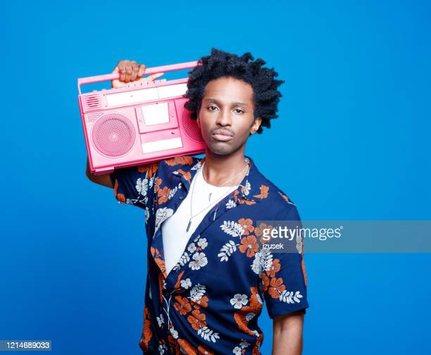confident man in hawaiian shirt holding pink boom box - pink colour stock pictures, royalty-free photos & images