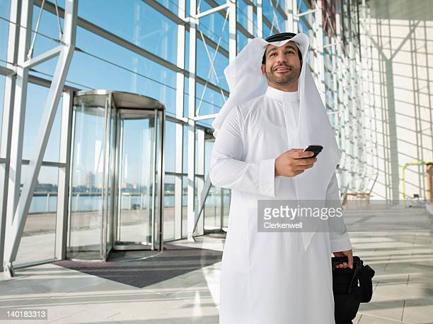 Confident man in kaffiyeh with suitcase