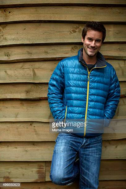 Confident man in winter coat against wooden wall