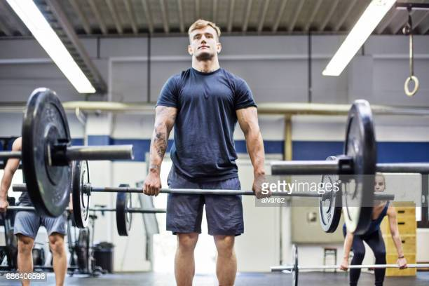 Confident man lifting dumbbell in health club