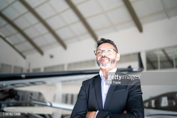 confident man looking away in a hangar - chairperson stock pictures, royalty-free photos & images