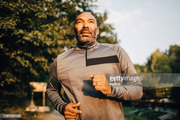 confident man looking away while jogging in park during sunset - men exercising stock pictures, royalty-free photos & images