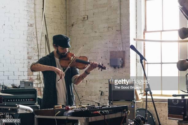 confident man playing violin - マイクスタンド ストックフォトと画像