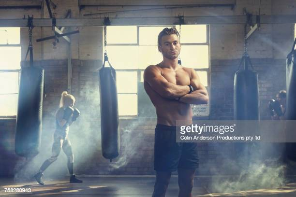 Confident man posing near punching bags in gymnasium