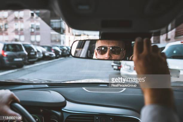 confident man sitting in a car and adjusting rear view mirror - rear view mirror stock pictures, royalty-free photos & images
