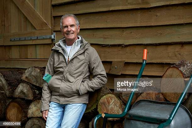 Confident man standing against stacked firewood