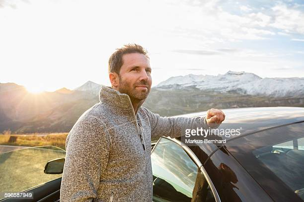 confident man standing next to his car. - ein mann allein stock-fotos und bilder