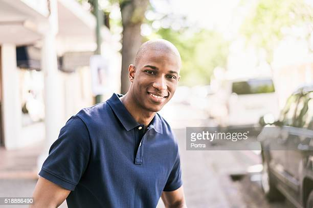 confident man standing outside shop - completely bald stock pictures, royalty-free photos & images